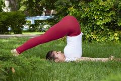 Jovem mulher atrativa bonita que estica o exerc?cio no parque imagens de stock