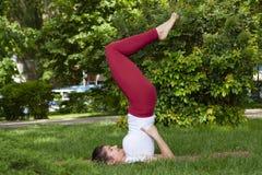 Jovem mulher atrativa bonita que estica o exerc?cio no parque foto de stock
