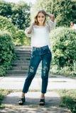 Jovem mulher atrativa bonita que levanta no parque da mola que veste w imagem de stock