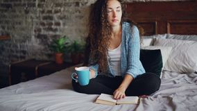 A jovem mulher atrativa com cabelo encaracolado escuro é página de giro do livro de leitura e literatura da apreciação que senta- vídeos de arquivo