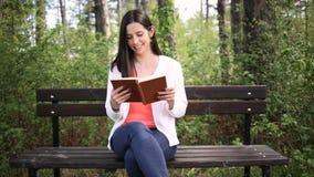 Jovem mulher atrativa com o livro velho no parque Deslize o slider filme