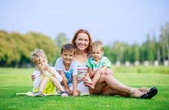 Jovem mulher atrativa com os filhos pequenos que sentam-se na grama no parque imagem de stock royalty free