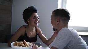 A jovem mulher atrativa com a toalha de banho em sua cabeça está sentando-se com seu noivo ou marido na mesa de cozinha tendo video estoque