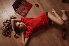 A jovem mulher atrativa com uma cara bonita relaxa no assoalho de madeira Fotografia de Stock