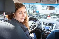 Jovem mulher atrativa como o motorista que olha para trás ao dirigir o carro fotografia de stock