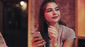 Jovem mulher atrativa da jovem mulher com os fones de ouvido em suas orelhas que escuta a música e que usa o smartphone Noite bor filme