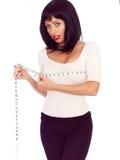 Jovem mulher atrativa de cabelo escura que mede seu busto com uma fita métrica Fotografia de Stock
