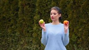 A jovem mulher atrativa do retrato no casaco azul escolhe entre a maçã verde e a laranja doce, decide morder a maçã vídeos de arquivo