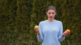 A jovem mulher atrativa do retrato no casaco azul escolhe entre a maçã verde e a laranja doce, decide morder a maçã video estoque