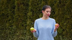 A jovem mulher atrativa do retrato no casaco azul escolhe entre a maçã verde e a maçã vermelha, decide morder a maçã verde vídeos de arquivo