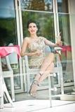 Jovem mulher atrativa elegante no vestido do laço que senta-se no restaurante, além das janelas Levantamento bonito da morena Fotografia de Stock