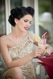 Jovem mulher atrativa elegante no vestido do laço que senta-se no restaurante, além das janelas Levantamento bonito da morena Fotografia de Stock Royalty Free