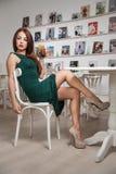 Jovem mulher atrativa elegante no vestido verde que senta-se no restaurante Ruivo bonito que levanta no cenário elegante com suco fotos de stock royalty free