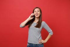 Jovem mulher atrativa em roupa listrada que fala no telefone celular, conversação agradável de condução isolado em brilhante fotos de stock royalty free