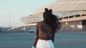 A jovem mulher atrativa em um equipamento à moda gerencie para a câmera e sorri seductively, continua a andar longe do filme