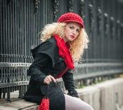 Jovem mulher atrativa em um tiro da fôrma do inverno. Rapariga bonita com o guarda-chuva vermelho na rua Foto de Stock