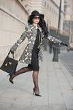 Jovem mulher atrativa em um tiro da forma do inverno Moça elegante bonita no levantamento preto na avenida Morena elegante fotografia de stock royalty free