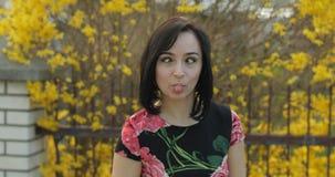Jovem mulher atrativa em um vestido com as flores que fazem as caras engra?adas fotografia de stock royalty free