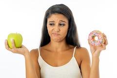 Jovem mulher atrativa em uma dieta que decide entre uma maçã e uma filhós fotografia de stock royalty free
