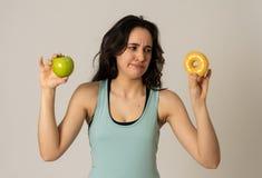 Jovem mulher atrativa em uma dieta que decide entre uma ma?? e uma filh?s foto de stock