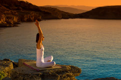 Jovem mulher atrativa em uma posição da ioga sobre uma praia bonita foto de stock royalty free