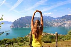 Jovem mulher atrativa entusiasmado no sportswear que estica apreciando a paisagem na manhã, Itália norte de Iseo do lago Humor al imagem de stock royalty free