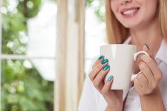 A jovem mulher atrativa está apreciando a bebida quente Imagens de Stock Royalty Free