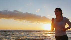 A jovem mulher atrativa está correndo ao longo do litoral no por do sol Contrate nos esportes - estilo de vida saudável Steadicam filme