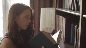 A jovem mulher atrativa está escolhendo um livro de texto nas prateleiras da biblioteca video estoque