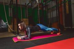 A jovem mulher atrativa está fazendo o exercício da prancha ao dar certo no gym Fotografia de Stock