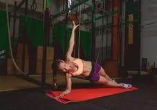 A jovem mulher atrativa está fazendo o exercício da prancha ao dar certo no gym Foto de Stock Royalty Free