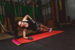 A jovem mulher atrativa está fazendo o exercício da prancha ao dar certo no gym Imagens de Stock