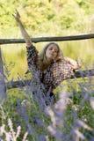 A jovem mulher atrativa está relaxando na grama e está esticando h Imagem de Stock Royalty Free