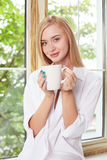 A jovem mulher atrativa está relaxando perto de uma janela Fotografia de Stock Royalty Free