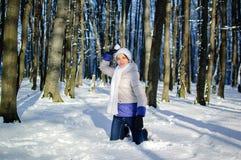 A jovem mulher atrativa está tendo o divertimento no parque nevado durante um tempo ensolarado no inverno A menina está jogando n fotografia de stock