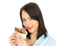 Jovem mulher atrativa feliz que come um no espeto de Donner fotos de stock