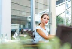 A jovem mulher atrativa lê um jornal que senta-se em um café Foto de Stock