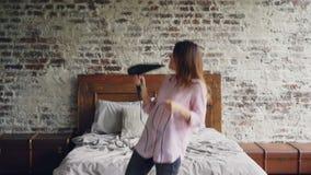 A jovem mulher atrativa na camisa e nas calças de brim é de dança e de canto guardando o secador de cabelo e usando o como o micr filme