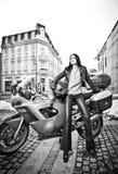 A jovem mulher atrativa na forma urbana disparou perto da motocicleta Moça elegante bonita no equipamento de couro preto Fotos de Stock
