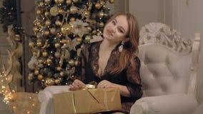 Jovem mulher atrativa na terra arrendada e nos olhares do laço em seu presente do Natal vídeos de arquivo