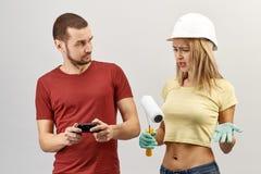 Jovem mulher atrativa nas calças de brim, na camisa amarela e em um capacete de segurança thr fotografia de stock