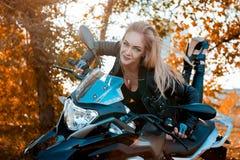 Jovem mulher atrativa no equipamento de couro preto com a motocicleta clássica do estilo fotografia de stock royalty free