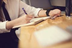 Jovem mulher atrativa no relógio esperto do frome da nota do escritório na mesa Fotografia de Stock Royalty Free