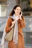 Jovem mulher atrativa no revestimento e no lenço que fala no telefone celular foto de stock royalty free