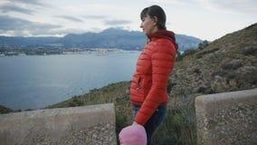 Jovem mulher atrativa no revestimento vermelho da bolha que anda com a criança na capa da rosa em uma estrada da montanha na cost vídeos de arquivo