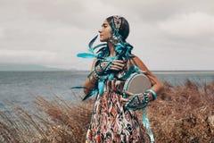 Jovem mulher atrativa no traje étnico em um campo no mar imagens de stock royalty free