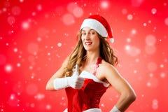Jovem mulher atrativa no traje de Santa Claus com polegares acima Imagens de Stock