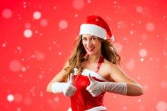 Jovem mulher atrativa no traje de Santa Claus com polegares acima Fotos de Stock