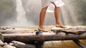Jovem mulher atrativa no vestido branco que anda com os pés descalços na ponte de madeira pequena sobre o rio da selva na florest vídeos de arquivo