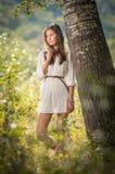 Jovem mulher atrativa no vestido curto branco que levanta perto de uma árvore em um dia de verão ensolarado Menina bonita que apr Foto de Stock